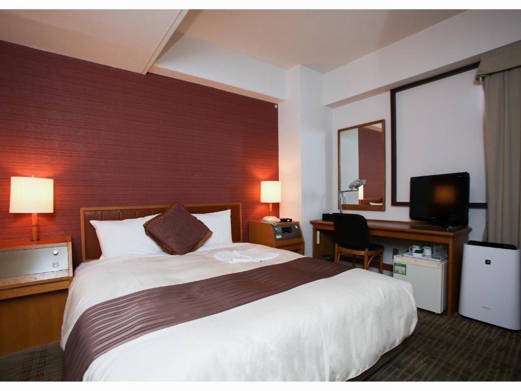 Un ou plusieurs lits dans un hébergement de l'établissement Koriyama Washington Hotel