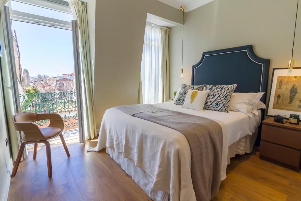 A bed or beds in a room at Bairro Alto Suites