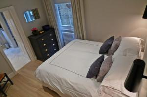 A bed or beds in a room at Luxe apartment in Kensington Olympia