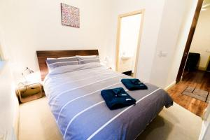 A bed or beds in a room at Flinders Lane - Studio Apartment