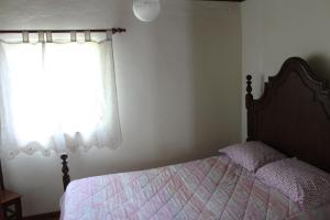 A bed or beds in a room at Alojamento da Ribeirinha