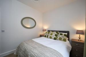 A bed or beds in a room at Camberley Luxury Apartments