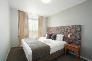 A bed or beds in a room at Quest Flemington Apartment Hotels