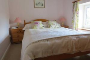 A bed or beds in a room at Garries Cottage