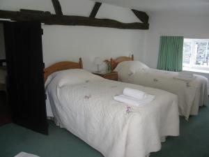 A bed or beds in a room at 2 Town Head Cottages