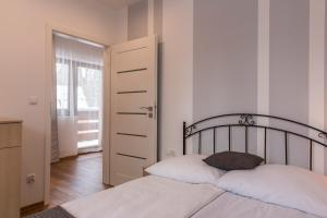 A bed or beds in a room at udanypobyt Apartament Skocznia