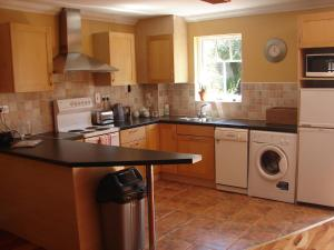 A kitchen or kitchenette at Courtyard Holiday Cottages