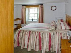 A bed or beds in a room at The Old Post Office, Holmrook