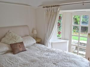 A bed or beds in a room at Lilac Cottage