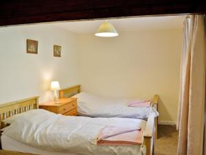 A bed or beds in a room at Granary Cottage III
