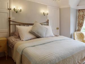 A bed or beds in a room at Priory Cottage