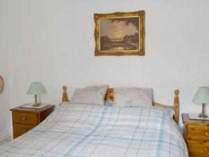 A bed or beds in a room at The Coachman'S Cottage