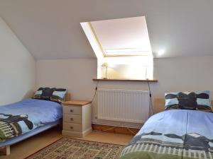 A bed or beds in a room at Red Barn Cottage