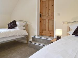 A bed or beds in a room at Cromwell Cottage