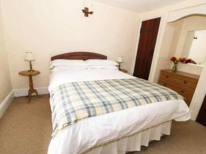 A bed or beds in a room at Raven cottage at Cwm Chwefru Cottages
