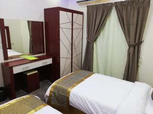 A bed or beds in a room at Al Momayaz Palace Hotel Suites
