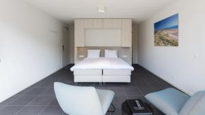 A bed or beds in a room at Duinhotel Tien Torens