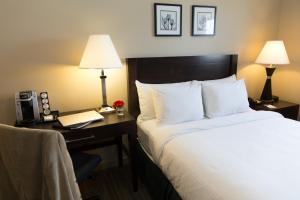 A bed or beds in a room at Capital Suites Yellowknife