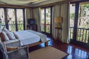 A bed or beds in a room at Ombak Luwung Beachfront Estate
