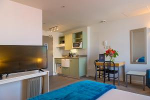 A television and/or entertainment center at Astelia Apartment Hotel
