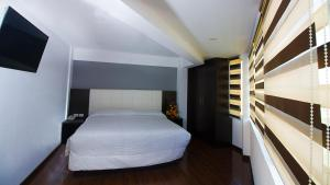 A bed or beds in a room at Apart Hotel Regina