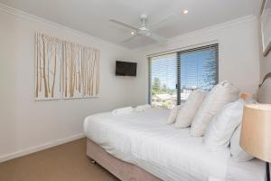 A bed or beds in a room at Cottesloe Beach Pines Apartment