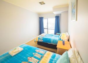 A bed or beds in a room at Glenelg Beachside Luxury Apartments