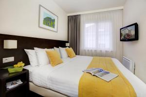 A bed or beds in a room at Citadines Sainte Catherine Brussels Aparthotel
