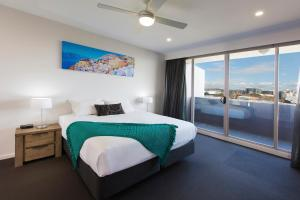 A bed or beds in a room at Chifley Apartments Newcastle