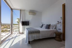 A bed or beds in a room at Cala Tarida Villa Sleeps 12 Pool Air Con WiFi