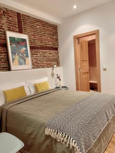 A bed or beds in a room at Aspasios San Mateo Boutique Apartments