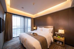 A bed or beds in a room at Howard Johnson Jinghope Serviced Residence Suzhou