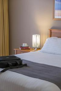 A bed or beds in a room at Waldorf Canberra Apartment Hotel