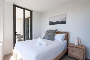 A bed or beds in a room at Luxury Apartment / / Moments to Lane Cove Village
