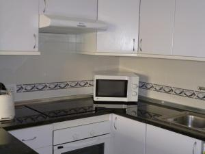 A kitchen or kitchenette at El Beril and Altamira apartments