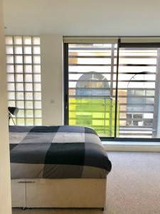 A bed or beds in a room at City Short Stays Aldgate East Studios