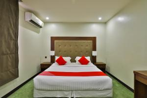 A bed or beds in a room at OYO 126 Dome Suites Al Mursalat