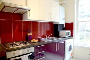 A kitchen or kitchenette at OYO Home Kings Cross-St Pancras Garden 4 Bedroom