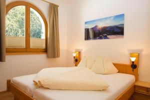 A bed or beds in a room at Apartments Landhof Ellmau Ellmau - OTR06502-EYD