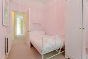 A bed or beds in a room at Cosy Three Bedroom Apartment In Fulham