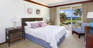 A bed or beds in a room at Whalers Cove in Poipu