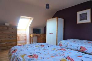 A bed or beds in a room at The Beltie Byre