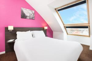 A bed or beds in a room at Aparthotel Adagio Access Strasbourg Petite France