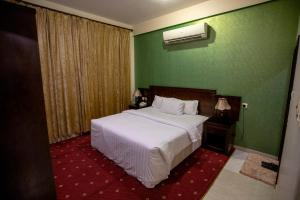 A bed or beds in a room at Raha Hotel Suites