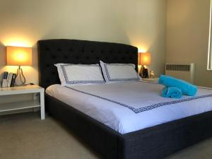 A bed or beds in a room at The Grove Luxury Apartment