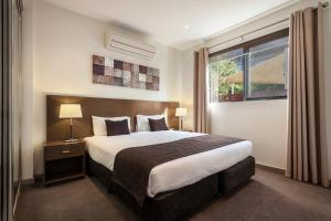 A bed or beds in a room at Quest Glen Waverley