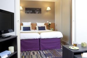 A bed or beds in a room at Aparthotel Adagio Paris Buttes Chaumont