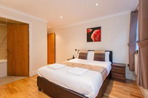 A bed or beds in a room at London Serviced Apartments