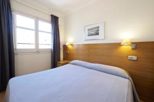 En eller flere senger på et rom på Apartamentos Atica