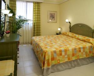 A bed or beds in a room at Paradise Court Aparthotel